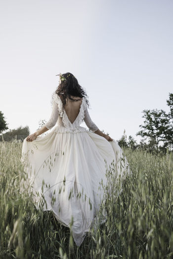 Bride walking in the countryside in a long wedding dress.