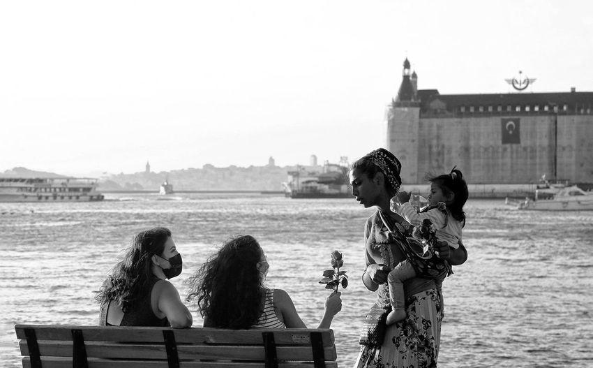 People sitting by sea against sky