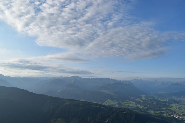 Aerial view of mountain range against cloudy sky