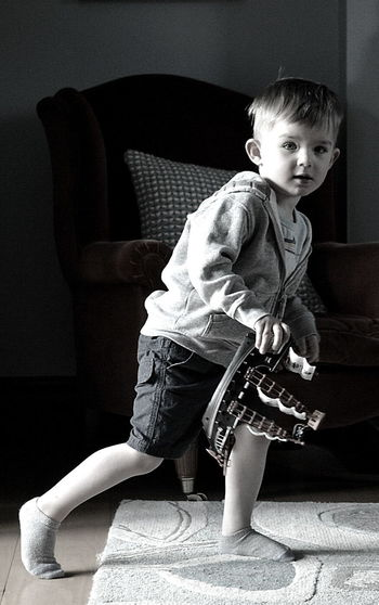 Portrait Of Boy With Musical Instrument At Home