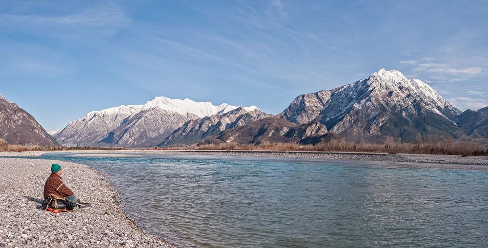 Man sitting at riverbank during winter