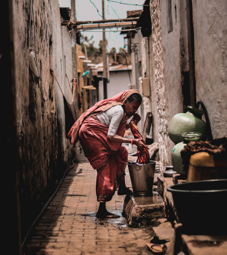 Side view full length of mature woman washing cloth at alley