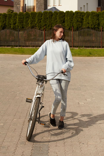 Full length of smiling woman with bicycle on road