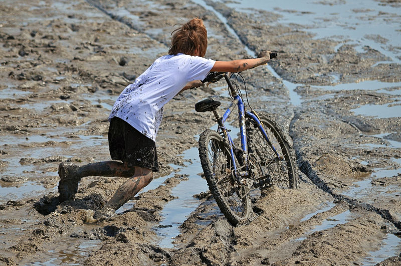 Rear View Of Girl With Bicycle Walking On Muddy Beach