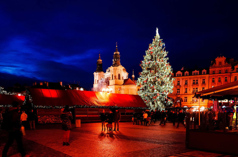 People Celebrating Christmas By Illuminated Buildings At Night