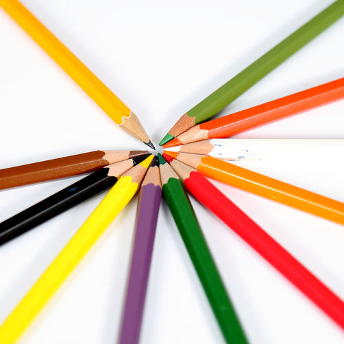 Close-up of multi colored pencils on white table