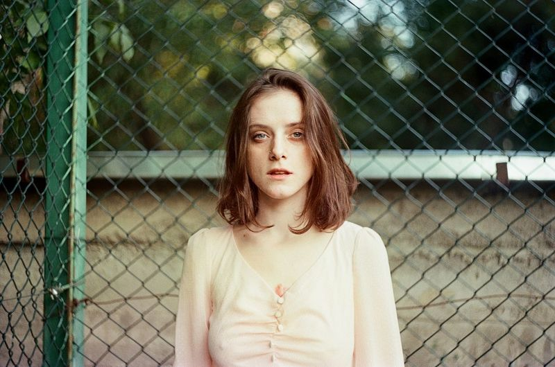Portrait of a beautiful young woman in chainlink fence