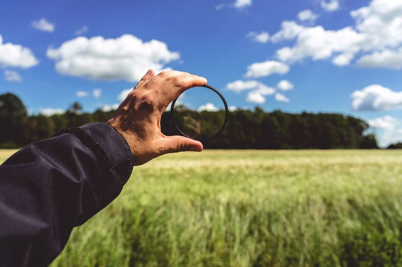 Cropped hand of person holding magnifying glass against sky