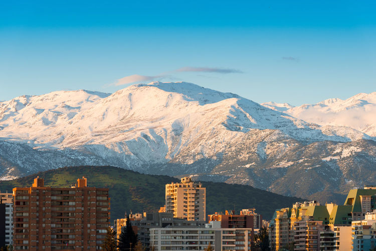 Skyline of residential apartment buildings with snowed los andes mountain range, santiago de chile