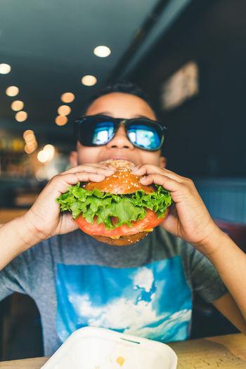 Close-up of boy eating hamburger