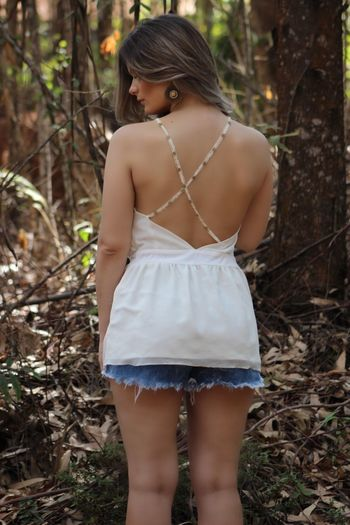 Rear view of sensuous woman standing against tree at forest