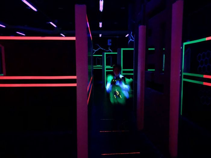 Rear view of people standing in illuminated dark room