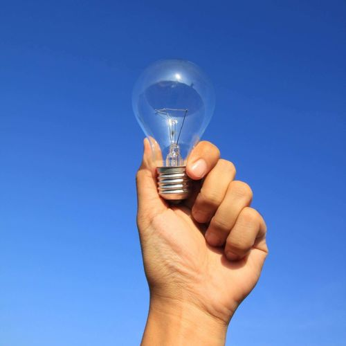 Lightbulb in hand Light Bulb Blue Clear Sky Lighting Equipment Human Hand Human Body Part Electricity  Fuel And Power Generation Outdoors Close-up One Person Day Sky People Nature Backgrounds