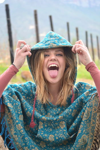 Portrait Of Playful Woman Wearing Hood While Sticking Out Tongue Outdoors