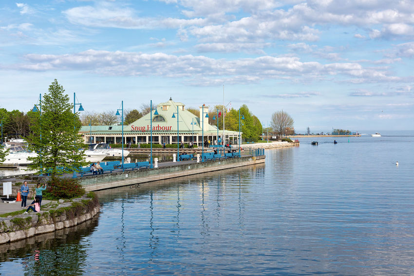 PORT CREDIT, CANADA - MAY 20, 2018: Beautiful panoramic view of the Snug Harbour Restaurant near the harbour Harbor Port Credit, Ontario Architecture Building Exterior Built Structure Canada Cloud - Sky Day Group Of People Incidental People Nature Nautical Vessel Outdoors Plant Reflection River Sky Snug Harbor Tourism Transportation Tree Visiting Visitor Water Waterfront