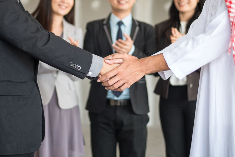 Midsection of man shaking hands with business person in office