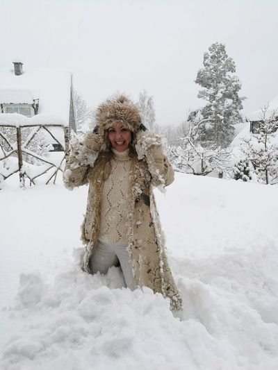 Portrait Of Cheerful Woman Standing On Snow Covered Field