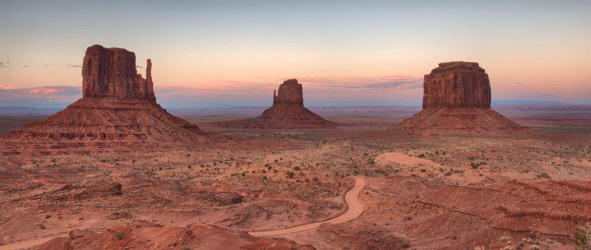 Rock formations in desert against sky during sunset