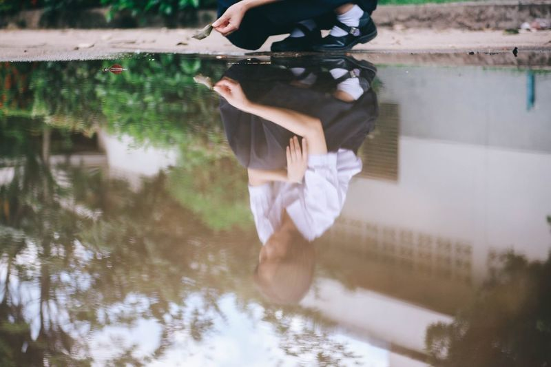 Woman Reflecting In Puddle