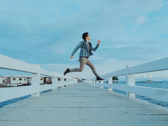 Full Length Of Man Jumping On Footbridge Over Sea Against Sky