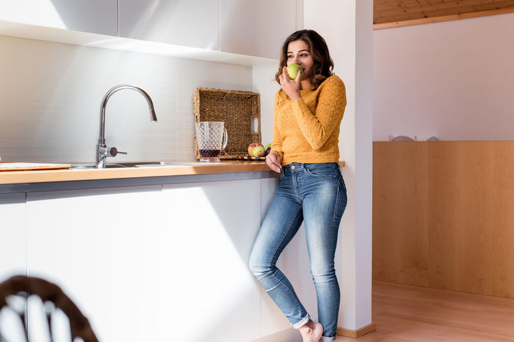 Full length of woman standing on table at home