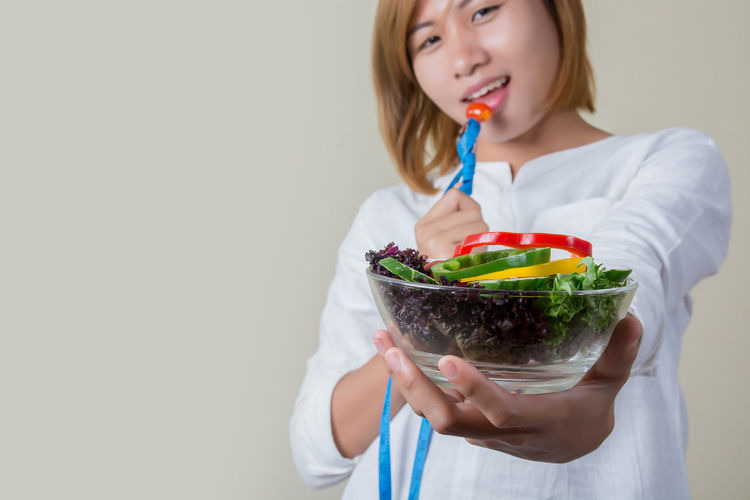 Portrait of young woman holding bowl with salad against white background