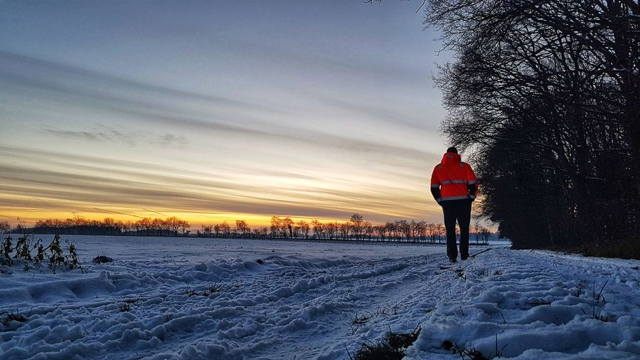 Rear view of man on snow covered field against sky during sunset
