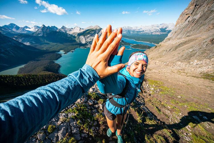 Portrait of happy friends on mountain against sky