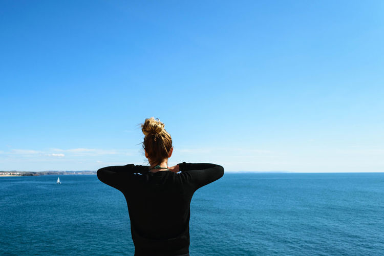 Rear View Of Woman Standing By Sea Against Clear Blue Sky