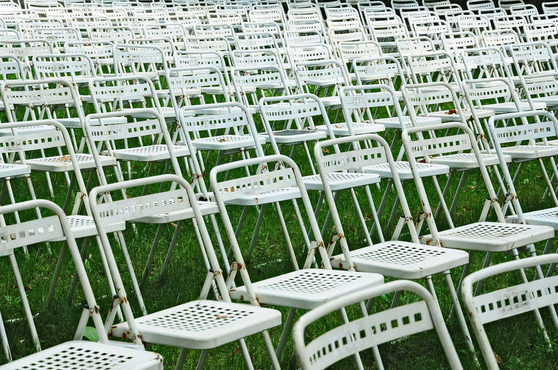 Full Frame Shot Of Empty Chairs Arranged On Grassy Field