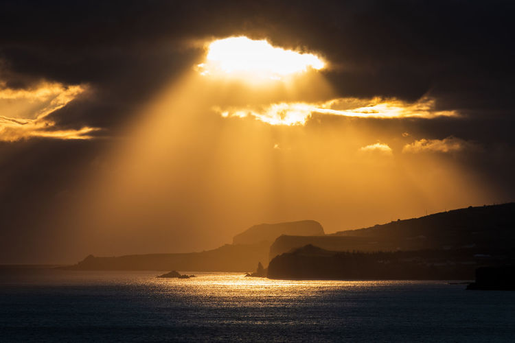 Sunlight streaming through clouds over sea during sunset