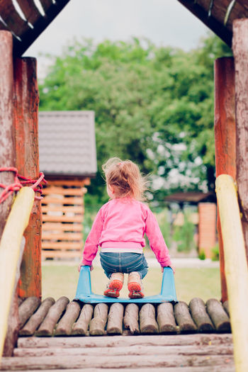 Rear view of girl crouching on slide