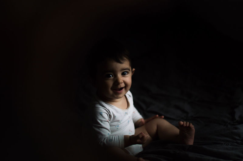 Portrait of smiling girl sitting on bed