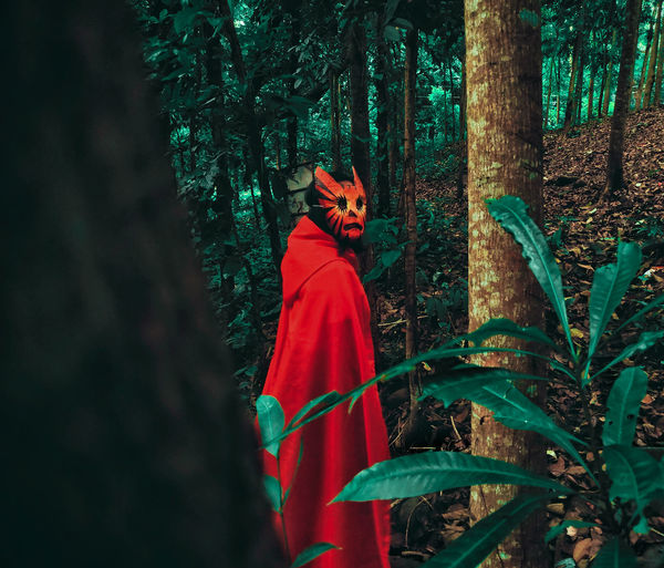 Woman wearing mask while standing amidst trees in forest
