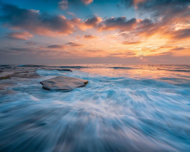 Rock steady Sea Water Sunset Sky Scenics - Nature Cloud - Sky Beauty In Nature Tranquility Nature Motion Land Tranquil Scene Horizon Over Water Horizon Beach Wave Outdoors Environment