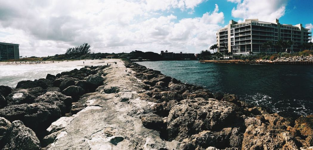 Scenic view of seawall against cloudy sky