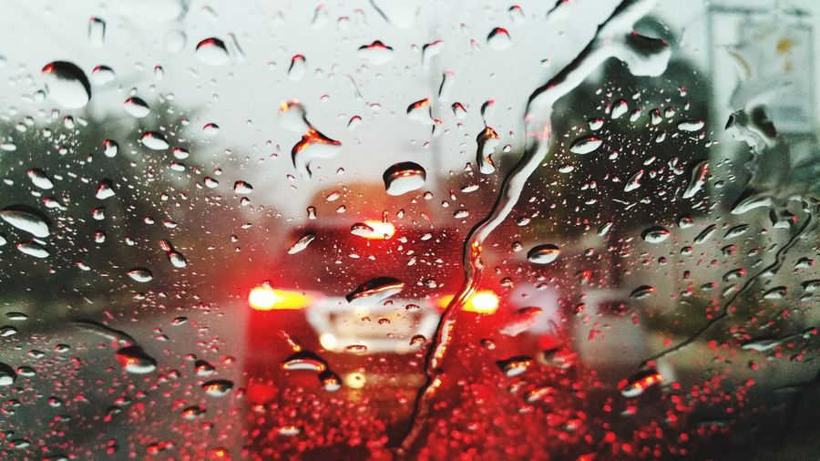 Close-up of car seen through raindrops on windshield