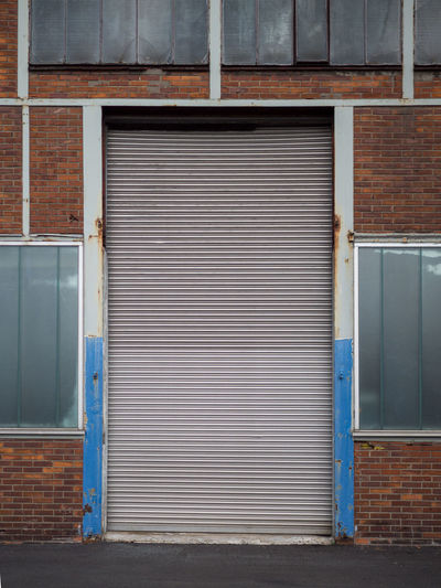 Alloy Architecture Brick Building Building Exterior Built Structure City Closed Day Door Entrance Garage Industry Iron Metal No People Security Shutter Steel Store Wall - Building Feature Warehouse Window