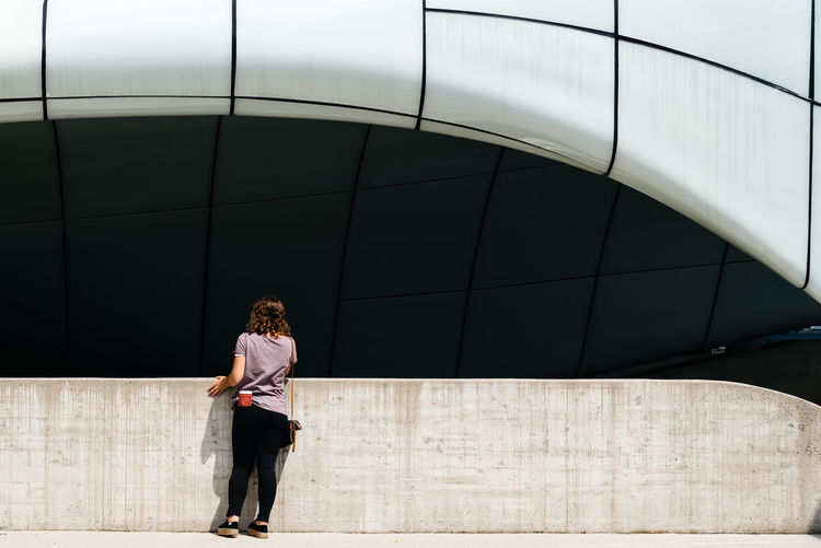 Woman at modern architecture building EyeEm Best Shots EyeEm Selects Modern Architecture Adult Architecture Attitude Building Exterior Built Structure Casual Clothing City Day Full Length Hairstyle Leisure Activity Lifestyles One Person Outdoors Real People Rear View Standing Three Quarter Length Walking Wall - Building Feature Women Zaha Hadid
