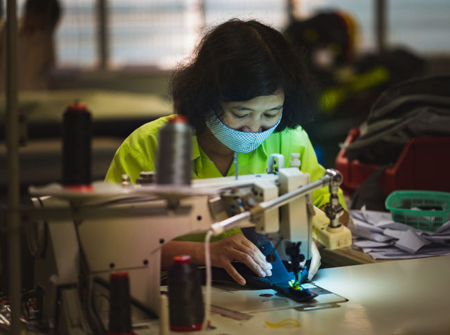 Overtime in a sewing company. ASIA Business Stories EyeEm Best Shots Light Sewing Sewing Machine Asia Women Close-up Concentration Indoors  Night Occupation One Person Overtime People Real People Sewing Women Skill  Technology Work Tool Working Yellow