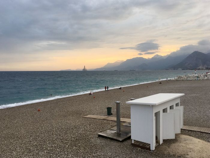 Portable toilet at beach during sunset