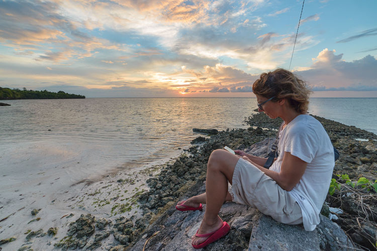 Water Sky Sea Beauty In Nature One Person Sitting Leisure Activity Sunset Cloud - Sky Beach Scenics - Nature Real People Full Length Lifestyles Land Rock Side View Solid Nature Outdoors Looking At View Hairstyle