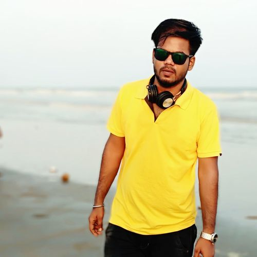 Portrait of young man wearing sunglasses while standing at beach
