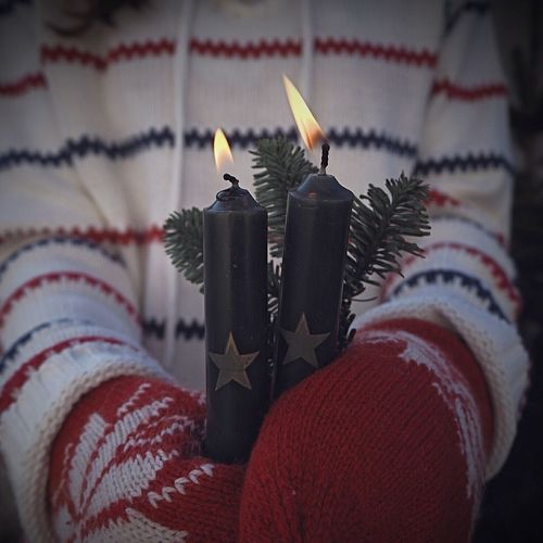 Midsection Of Child Holding Lit Candles During Winter