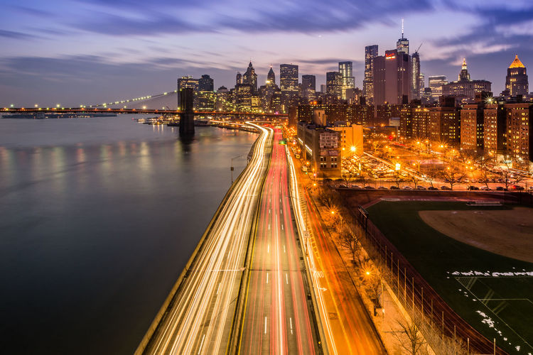 High angle view of light trails on city street by east river at dusk