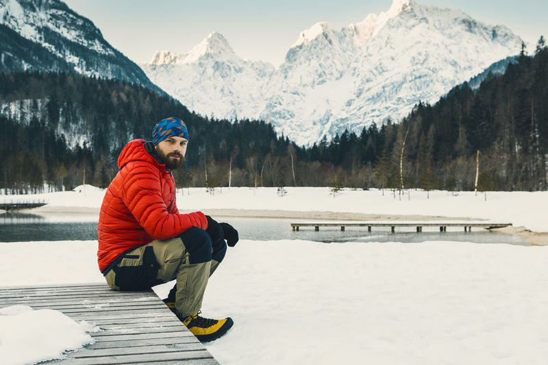 Portrait of man sitting at snow covered lakeshore against mountains