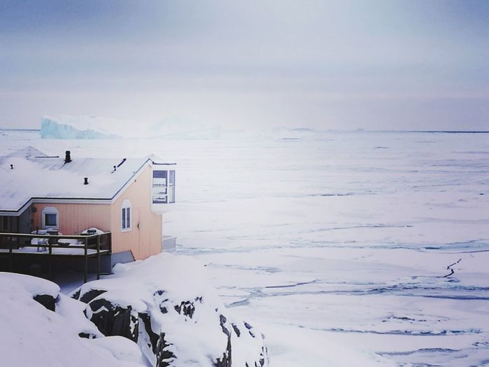 Snow Covered Houses By Sea Against Sky
