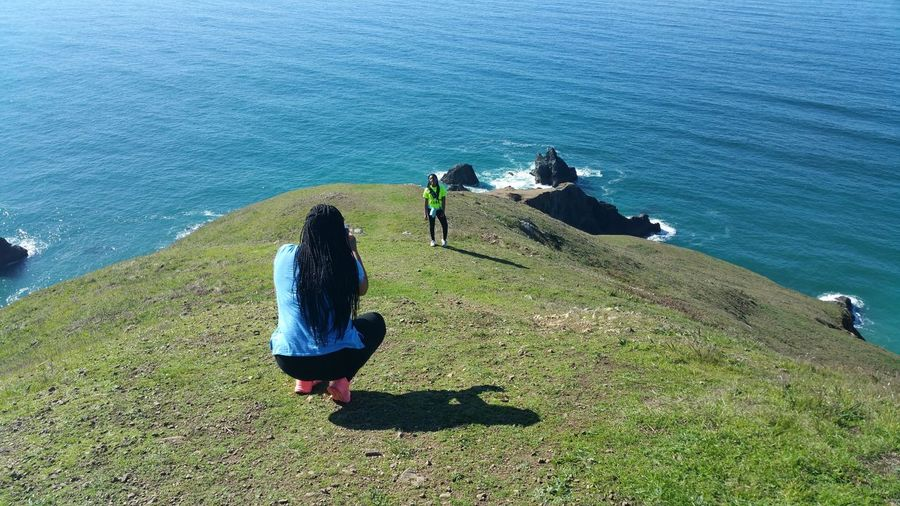 Woman Crouching With Friend On Field Against Sea