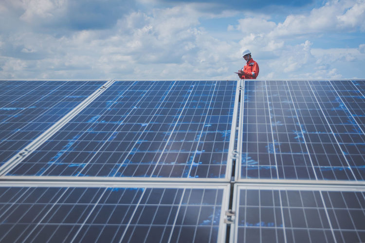 Engineer standing amidst solar panel against cloudy sky
