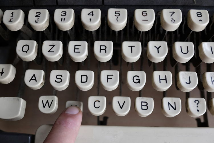 Cropped Image Of Person Typing On Typewriter